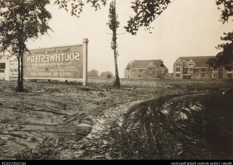 "An old photo of a muddy construction site with a few buildings in the background and a sign in the middle ground that reads, ""Here is being erected: Southwestern 该 College of the Mississippi Valley"""