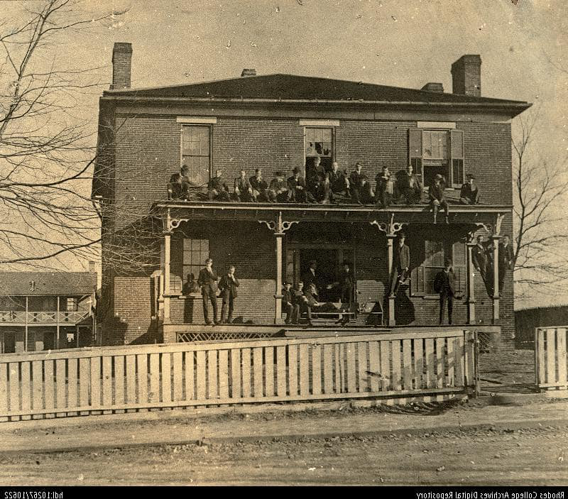 Old photo of students on the porch and top of the portico of a building