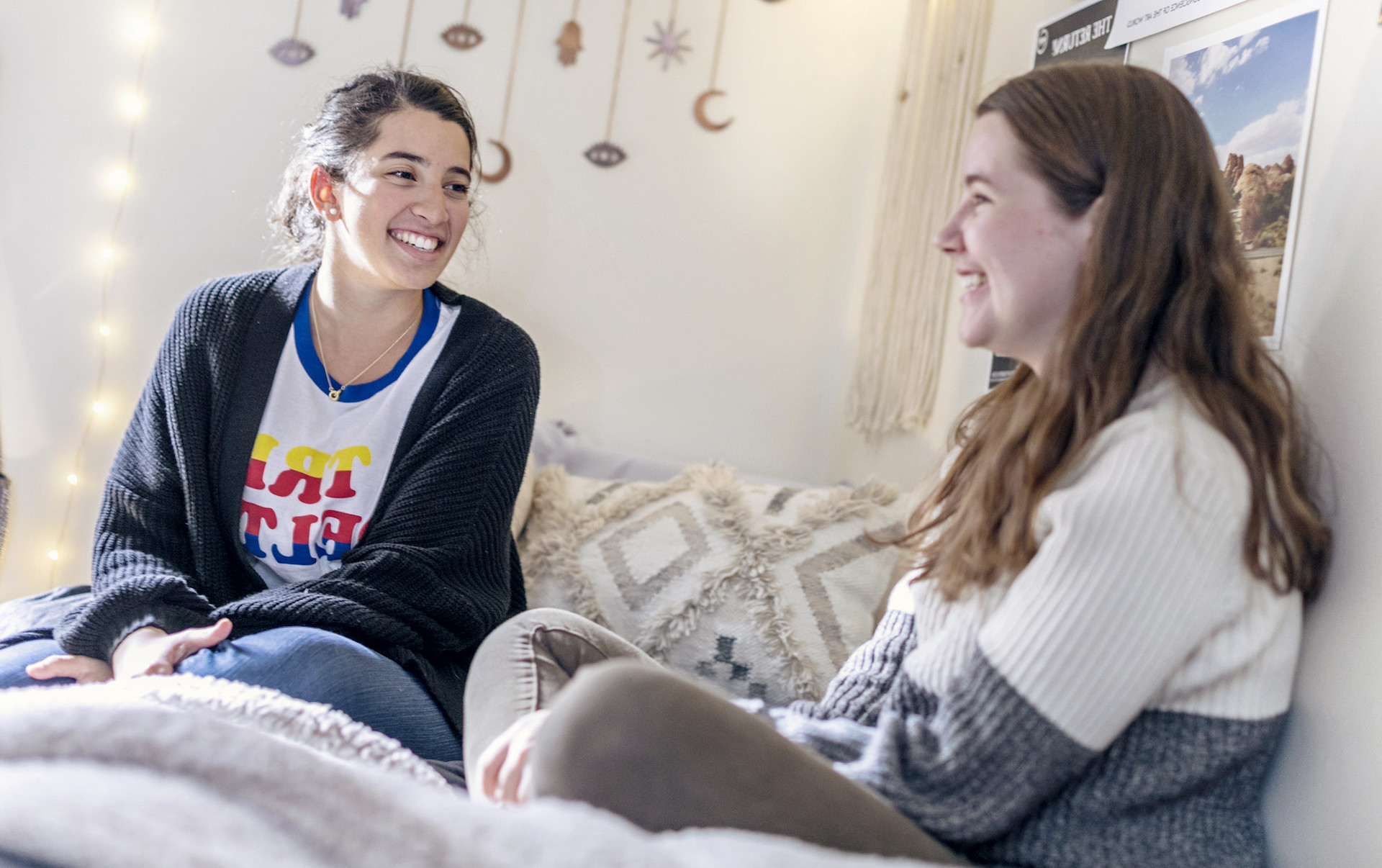 Two women sitting on a dorm room bed, talking and laughing. The white walls behind them are decorated with fairy lights, a poster of mesas in the southwestern US, and a mobile hanging with stars, moons, and all-seeing eyes.