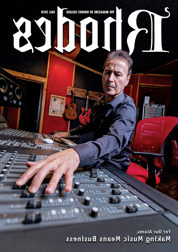 a man on the cover of Rhodes magazine works a sound board