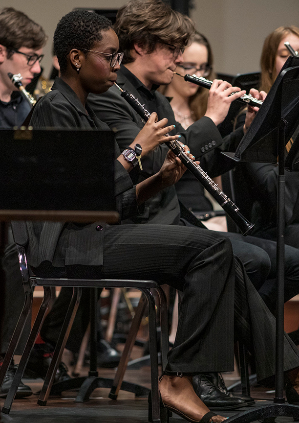 a woman plays a reed instrument in the orchestra