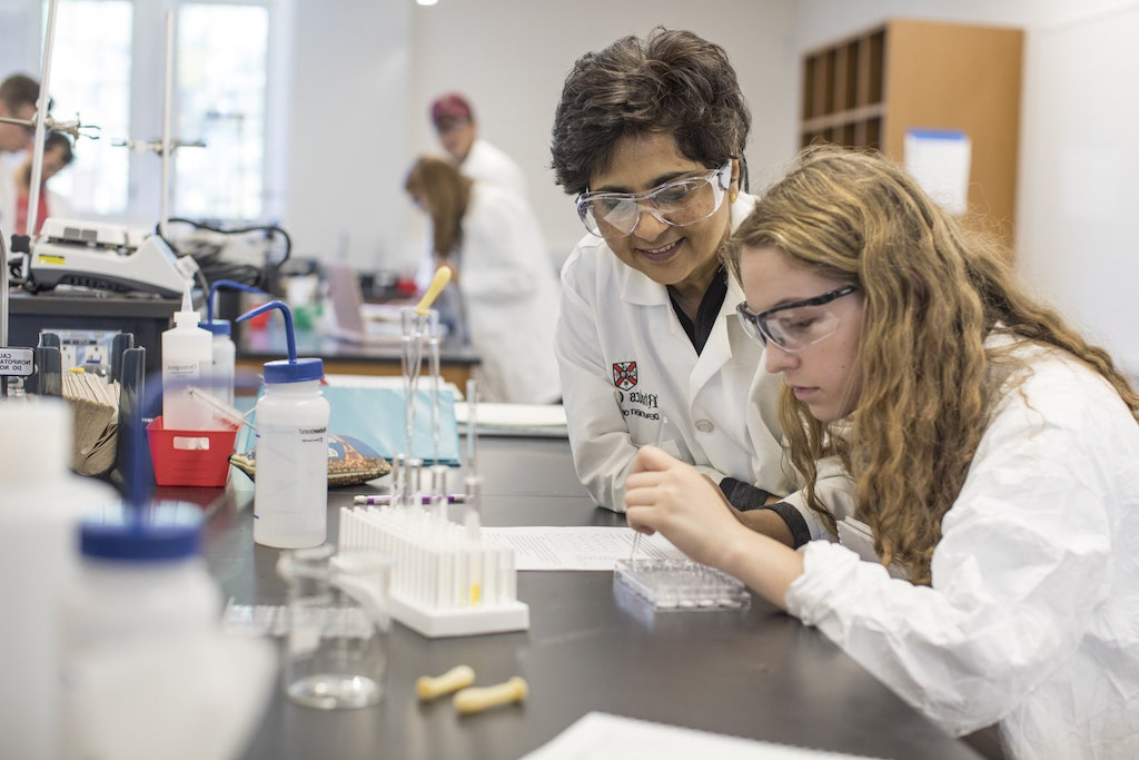 A professor helps her student, who is examining her lab experiment.