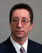 a man with short dark hair and glasses