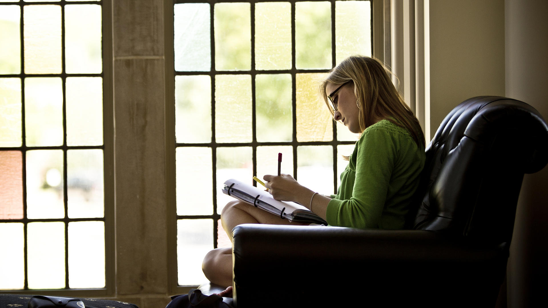 Woman studying in front of stained glass window