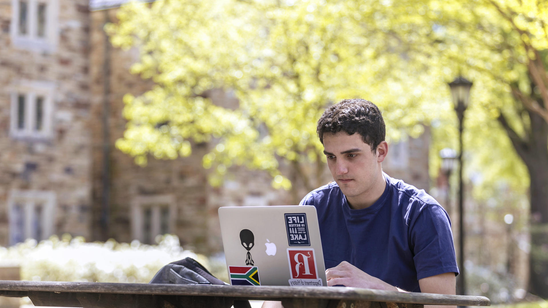 a male student looking at a laptop
