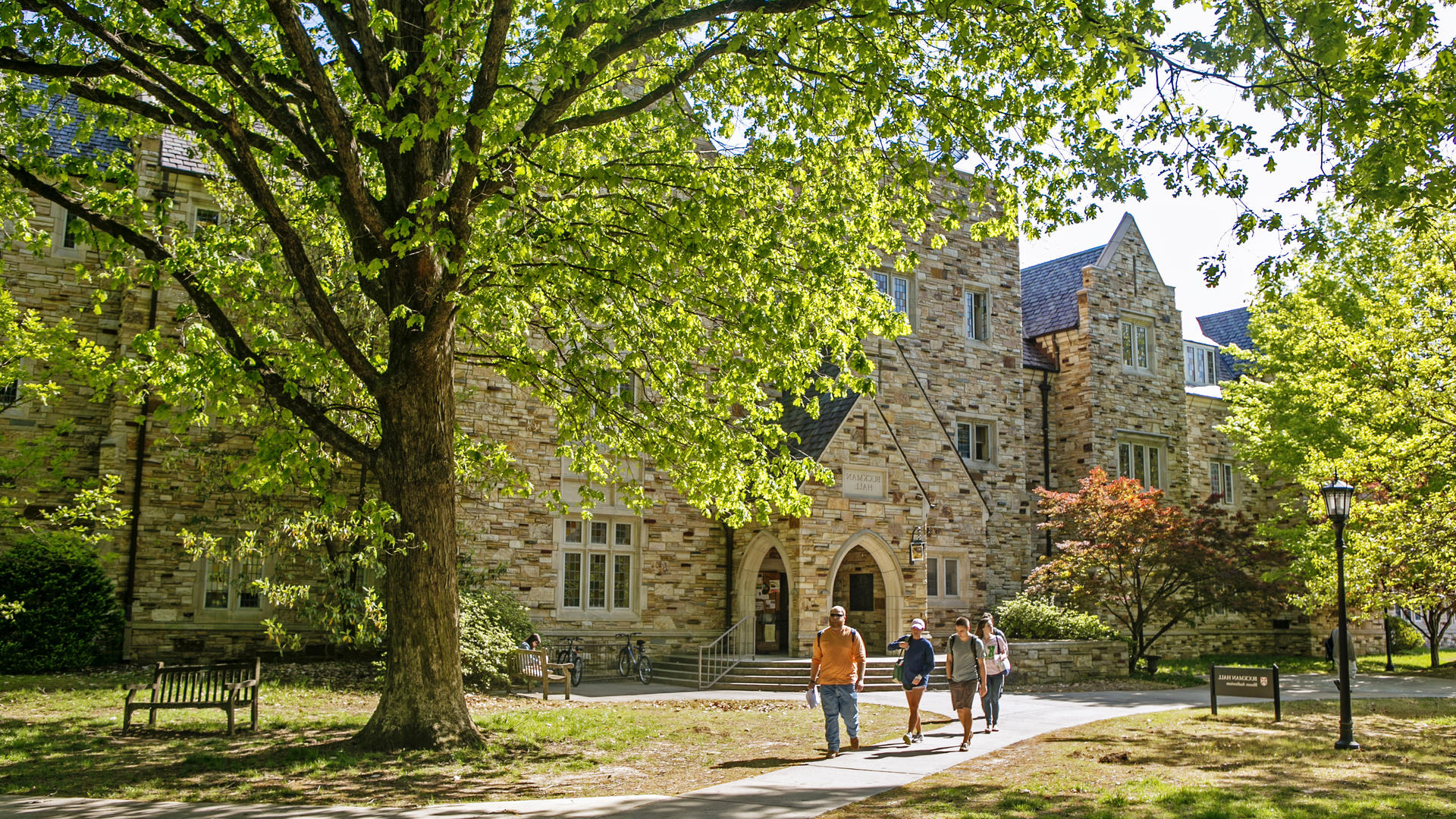 a Gothic stone building with a sign saying Buckman Hall