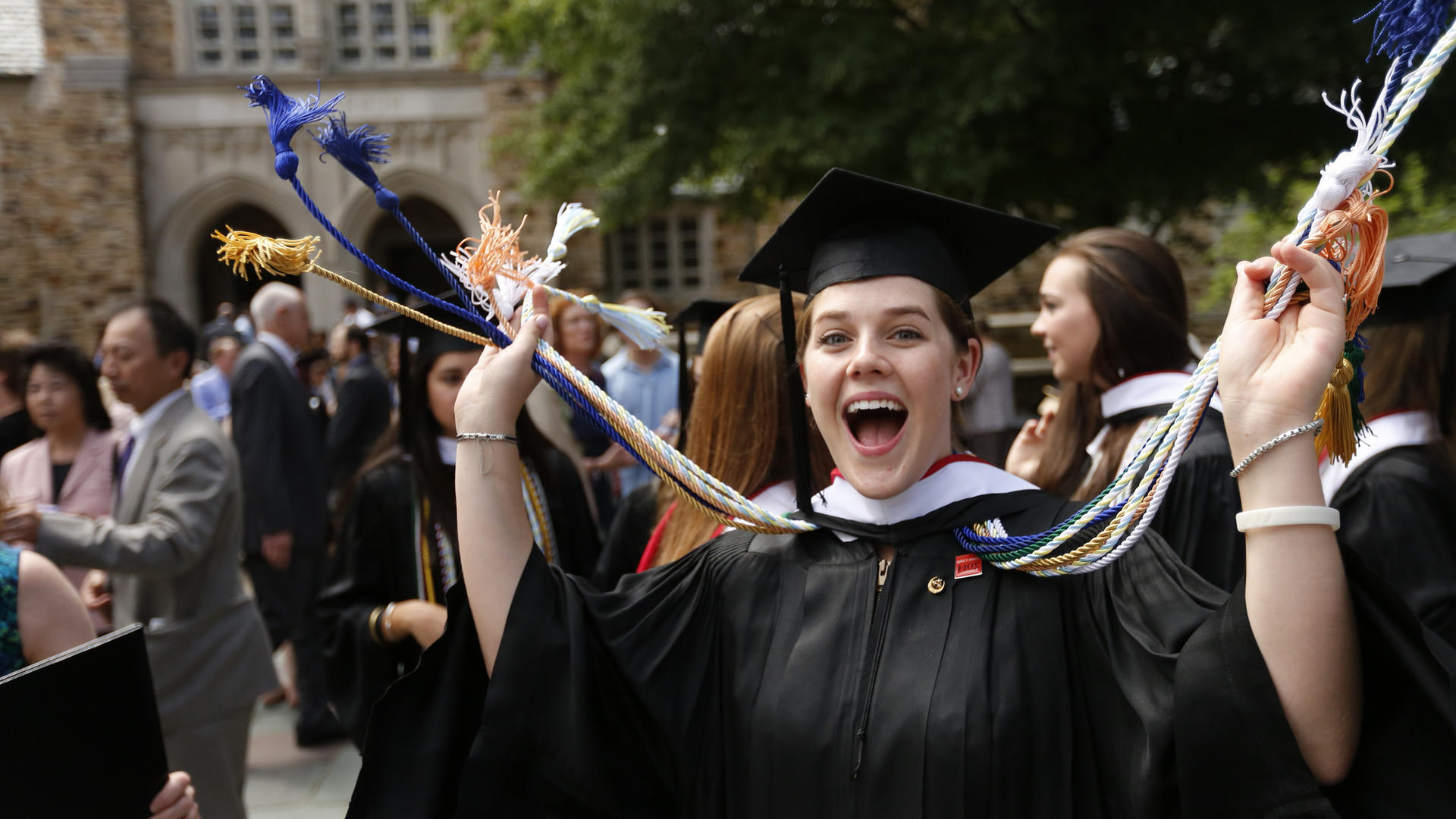 An excited student in graduation regalia smiles at the camera