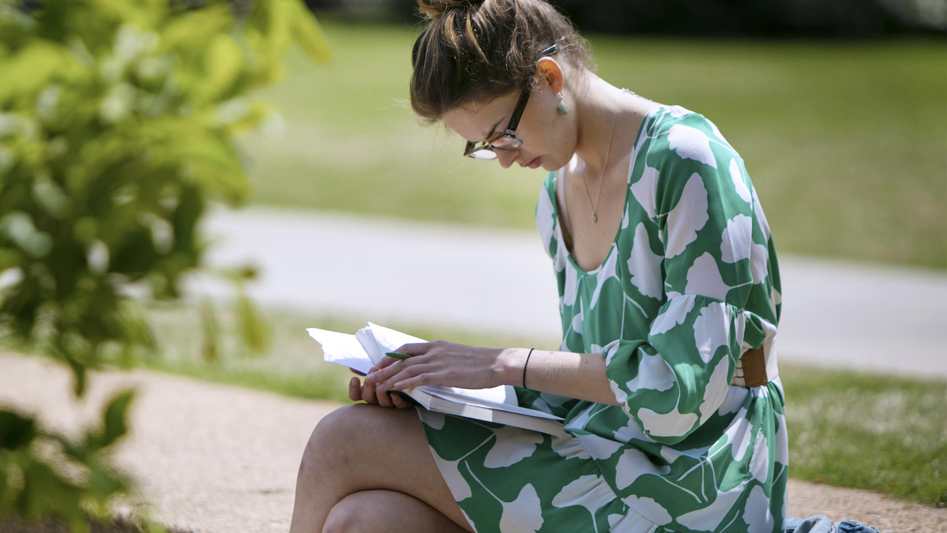 A young woman with glasses in a green dress sits at the top of a stone ampitheatre reading a book.