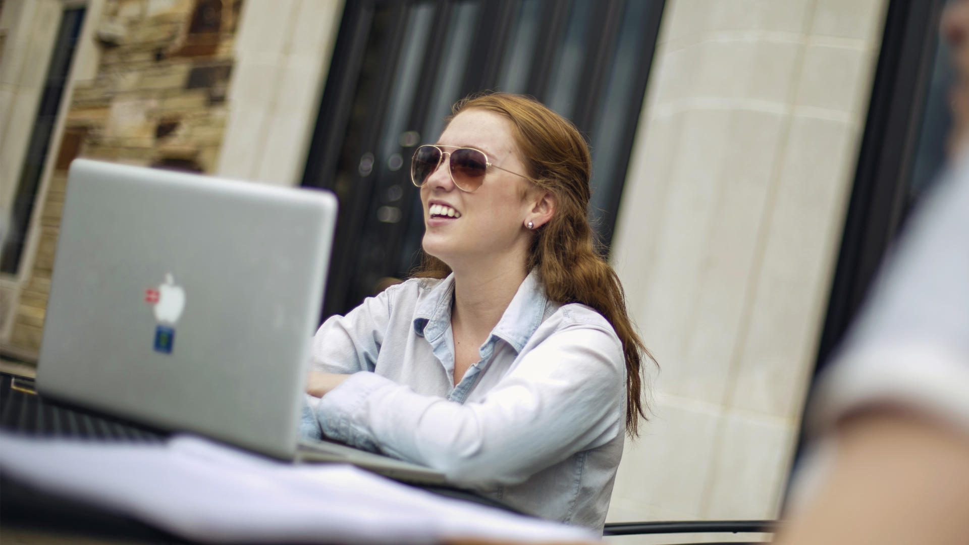 A woman wearing sunglasses sits on the Lynx Lair patio at a table with a laptop and papers