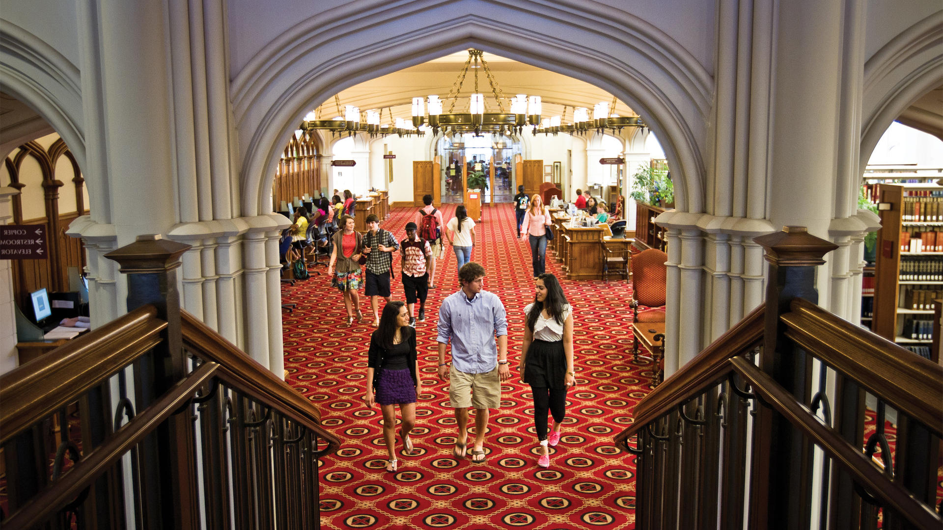 Three students approach the stairs on the main floor of the library