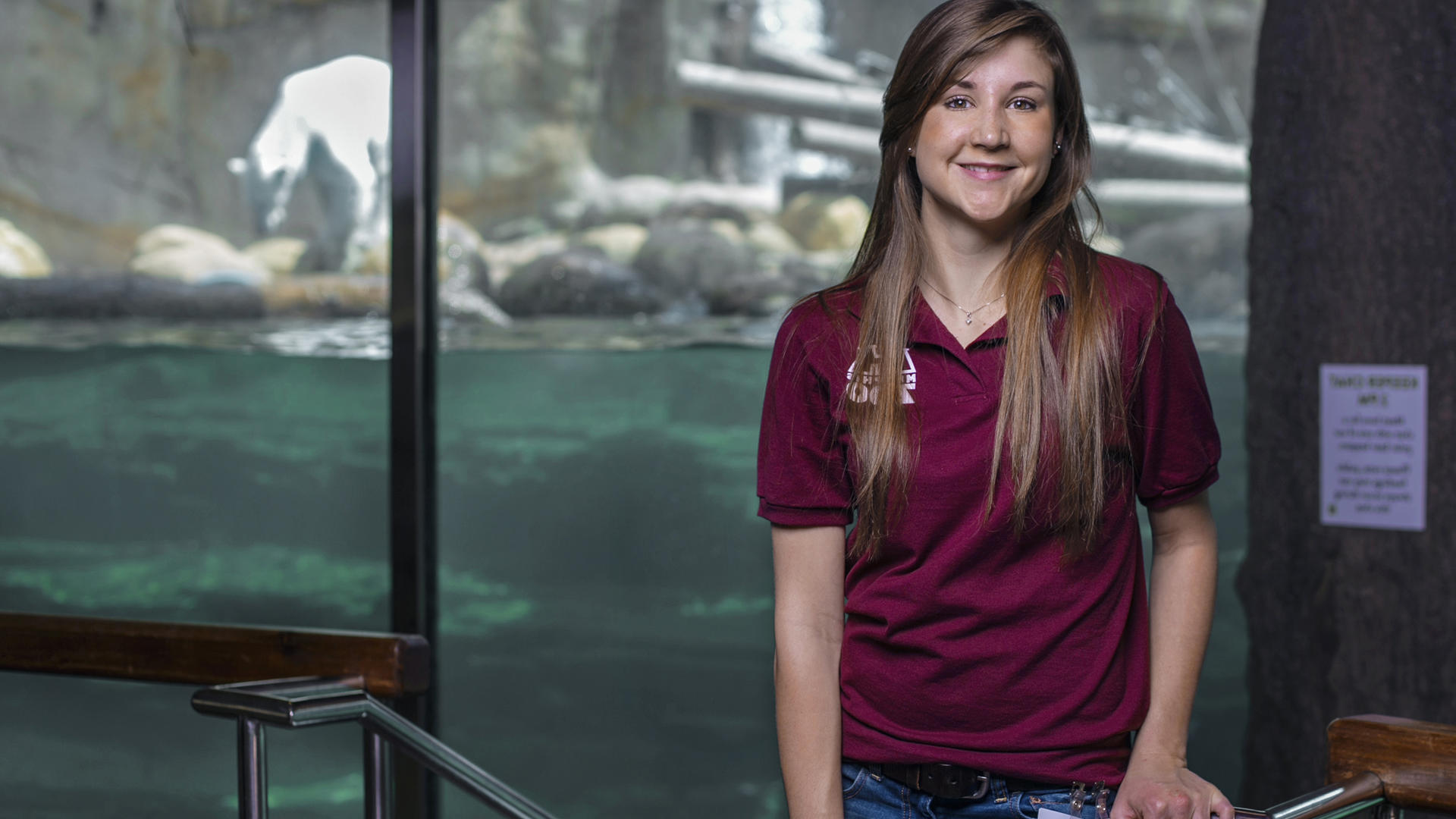 a student standing in front of an aquatic zoo exhibit