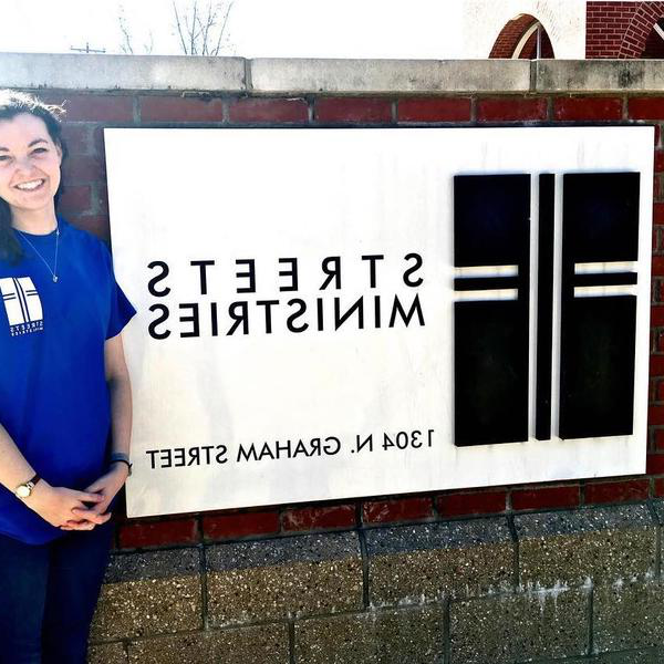 A woman in a blue t-shirt stands in front of a sign inlayed in brick that says Streets Ministries