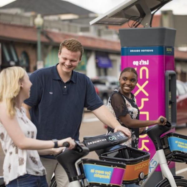 Two student rent bikes from a ridesharing station.