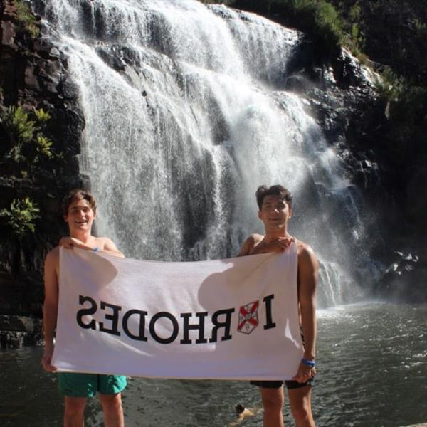 "Two young men stand with an ""I Heart Rhodes"" banner in front of a rushing waterfall."
