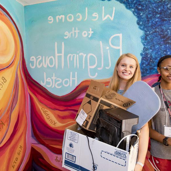 two female students carry boxes in front of a mural