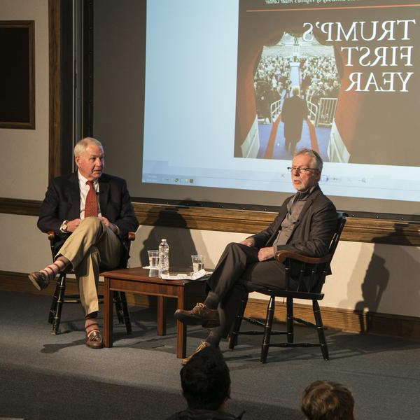Two professors sit in conversation on a stage