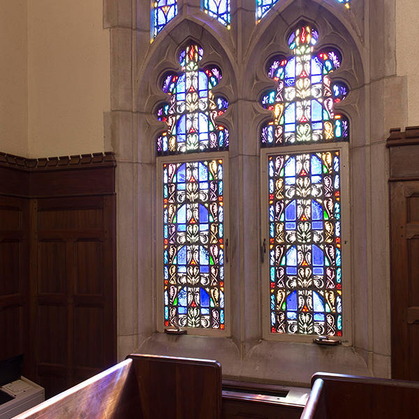 stained glass windows with a church pew