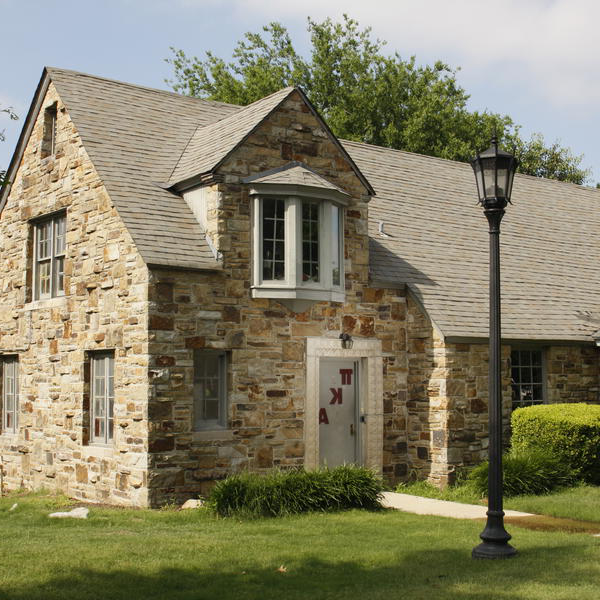 A stone house with a lamp post in front
