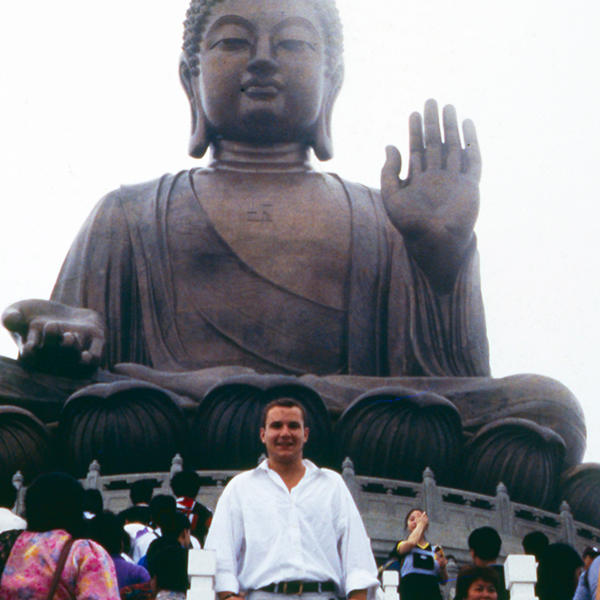 a young man stands in front of a huge statue of the Buddha