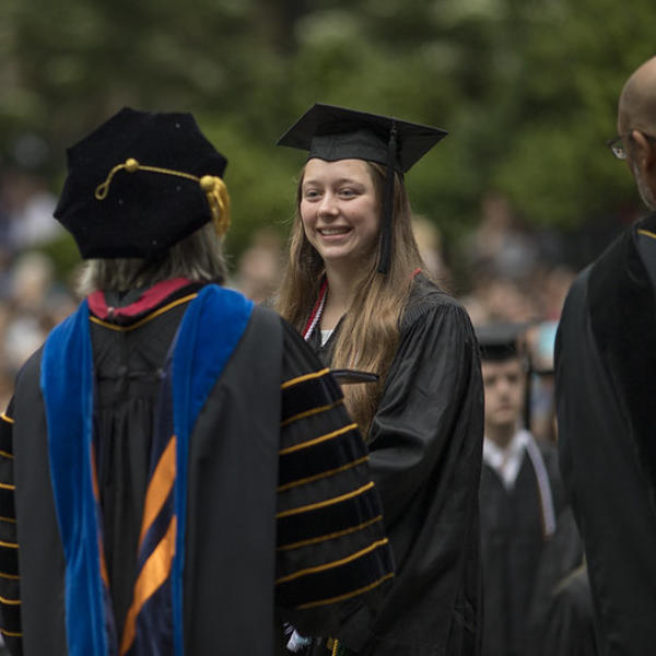A student in her commencement regalia receives her degree from the president.