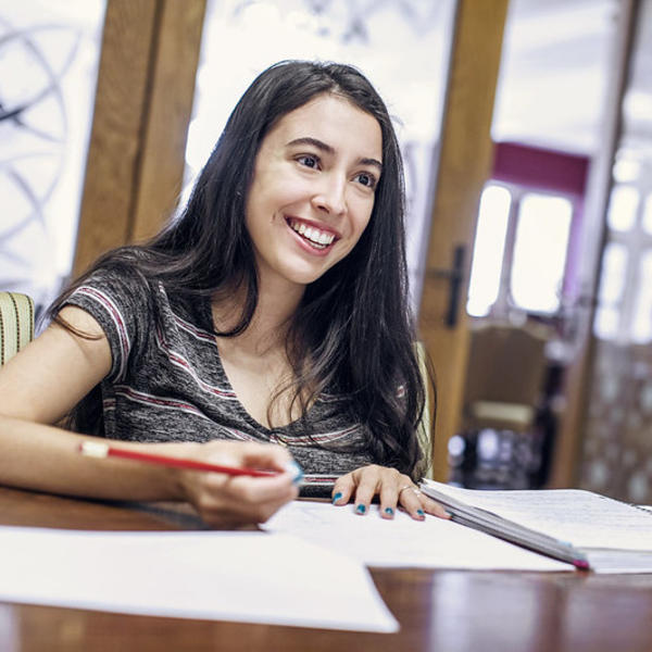 A dark haired woman looks up from where she has been writing out her class schedule and smiles at the person across the table.