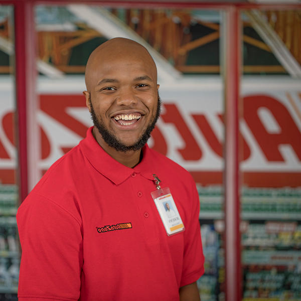 a male standing in front of an AutoZone sign smiles at the camera