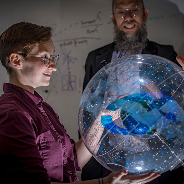 a student holds a globe showing the constellations while a professor looks on