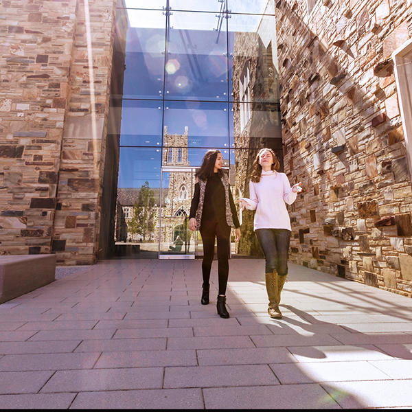 two female students walk in front of a stone and glass building