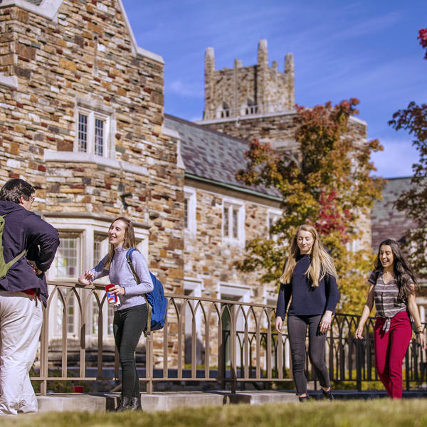 Groups of students congregate in front of a stone building.