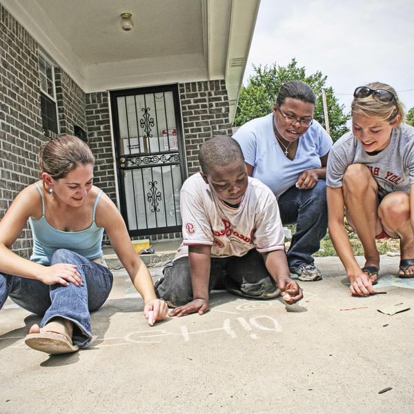 students and a young boy are crotched down writing on a sidewalk in chalk