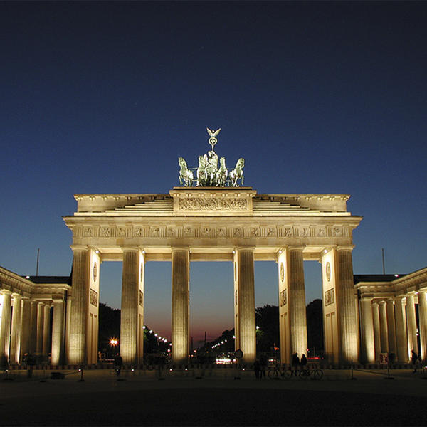 Tall arch with multiple columns lighted at night