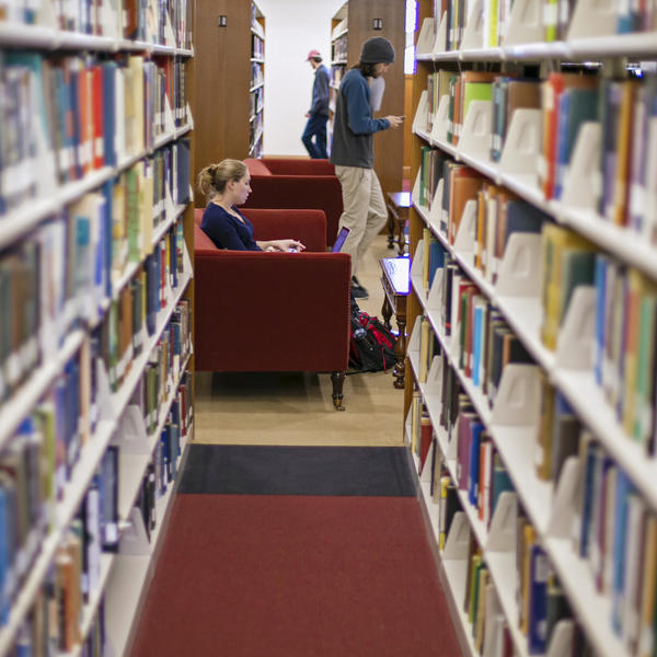 Between two rows of bookshelves, a student sits in a chair and another walks by
