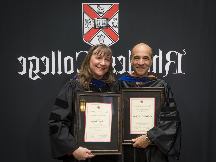 two college professors holding awards standing in front of black backdrop with a college logo printed on it