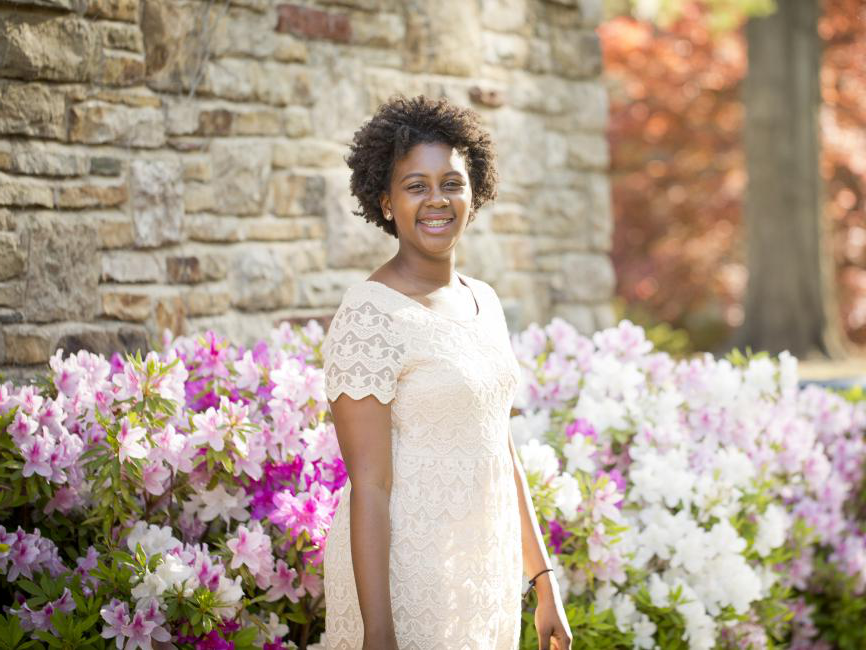 an African American female student standing near blossoming flowers