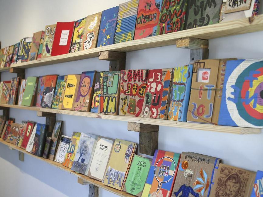 various shelves of books and blocks of colorful art
